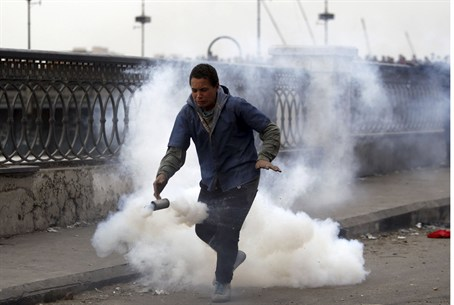 A protester flees from tear gas fired by riot
