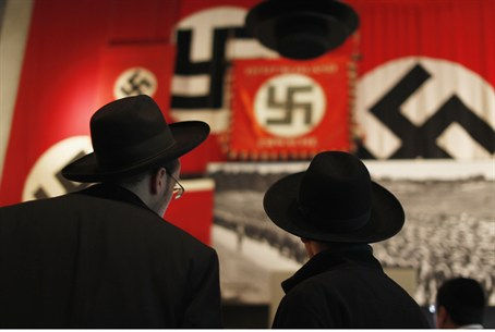 Jews look at a display of Nazi flags