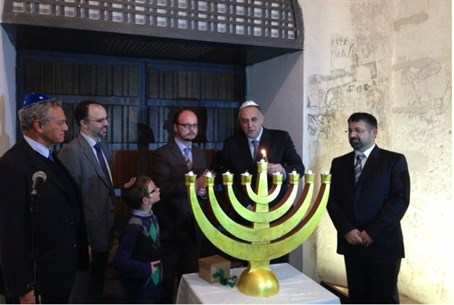 Rav Pinhas (center, with glasses), leads Hanukkah service in Palermo