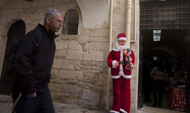 A Jewish man walks next to a Santa Claus doll in a shop in Jerusalem's Old City
