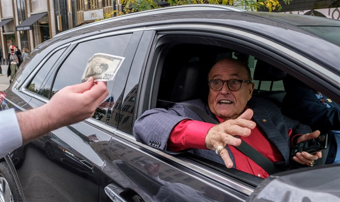 Former New York City Mayor Rudy Giuliani drives by protest